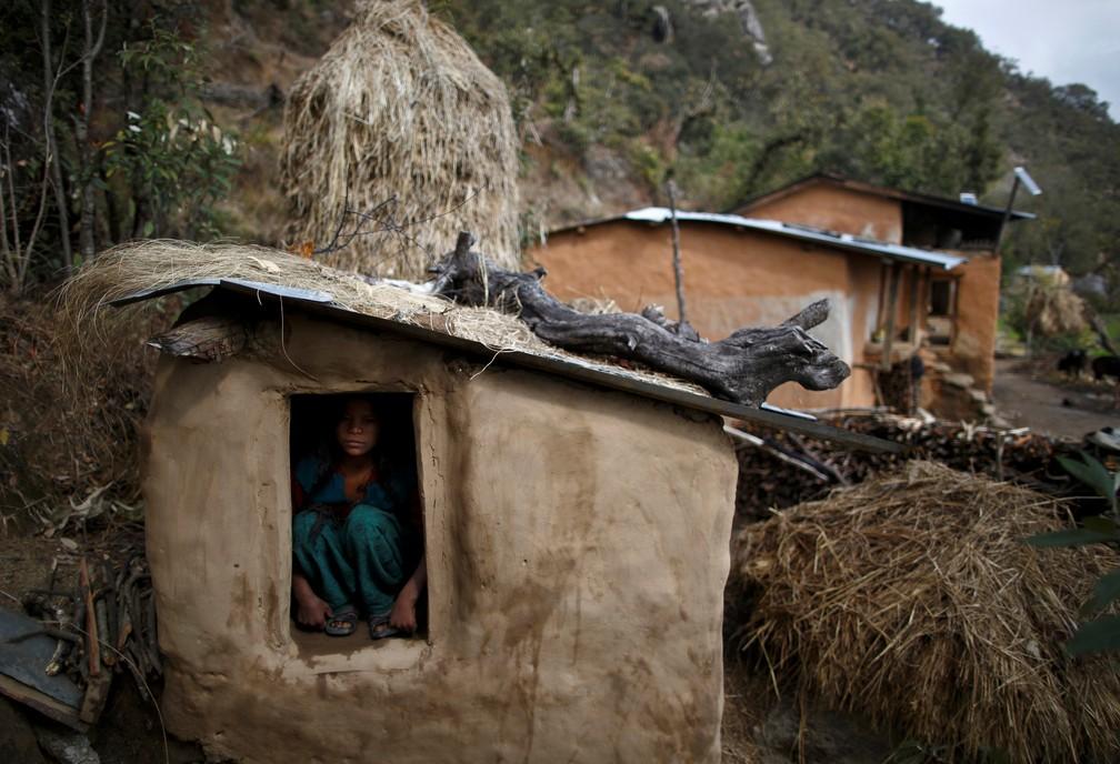 Uma adolescente de 14 anos dentro de uma barraca para mulheres que estão menstruadas, em imagem de 16 de fevereiro de 2014 — Foto: Navesh Chitrakar/Reuters