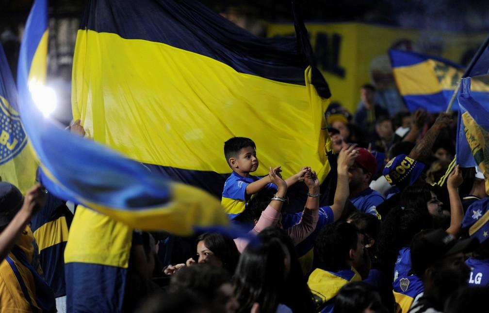 Criança no meio da festa com bandeiras dos torcedores do Boca Juniors antes da viagem do time para a final da Taça Libertadores — Foto: REUTERS/Stringer