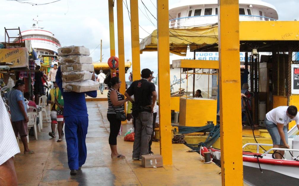 Homem carrega cinco caixas com produtos até embarcação atracada em balsa na orla do Rio Negro em Manaus (Foto: Leandro Tapajós/G1 AM)