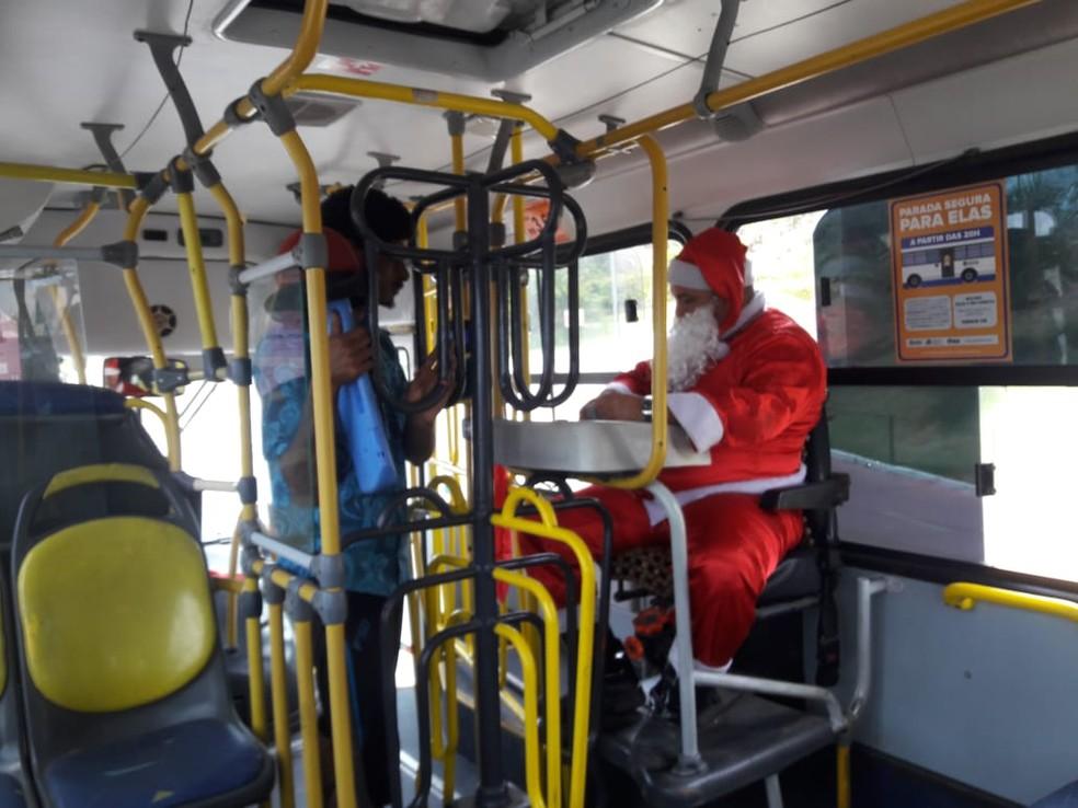 Cobrador vestido de Papai Noel chama a atenção de passageiros em Maceió — Foto: Thamires Ribeiro/G1