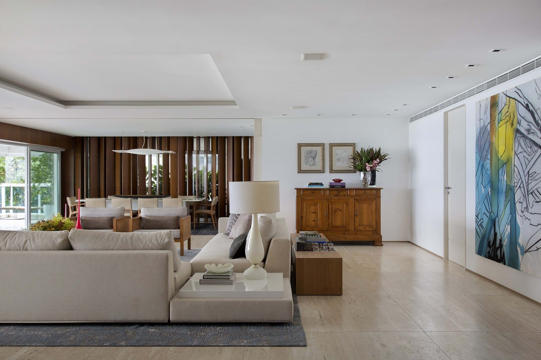 Sala com piso em travertino, sofás cinzas, desenho na parede e móvel de madeira.