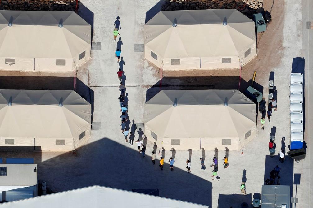 Crianças imigrantes, mmuitas delas separadas dos pais sob a política de tolerância zero do governo Trump, caminham em fila entre barracas de composto perto da fronteira mexicana em Tornillo, no Texas, EUA (Foto: Mike Blake/Reuters)