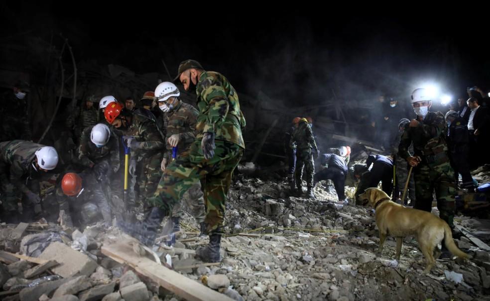 Soldados vasculham área bombardeada na cidade de Ganja neste sábado (17) — Foto: Umit Bektas/Reuters