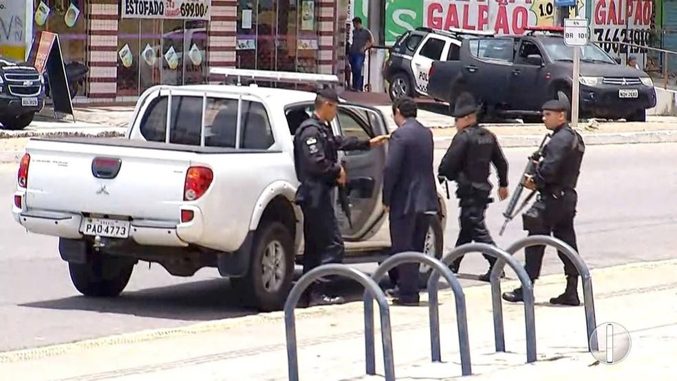 Gerente do Banco do Brasil deixa agência escoltado por policiais, após ficar mais de 12 horas sob poder de criminosos (Foto: Inter TV Cabugi)
