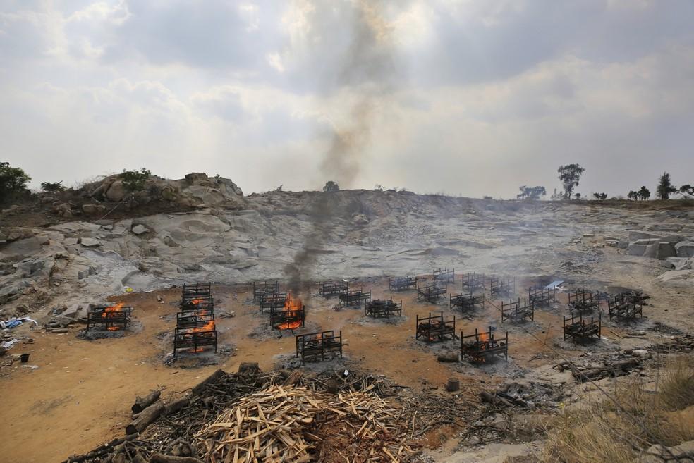 Piras funerárias de 25 vítimas da Covid-19 queimam em crematório a céu aberto criado em uma pedreira de granito nos arredores de Bengaluru, na Índia, em 5 de maio de 2021 — Foto: Aijaz Rahi/AP