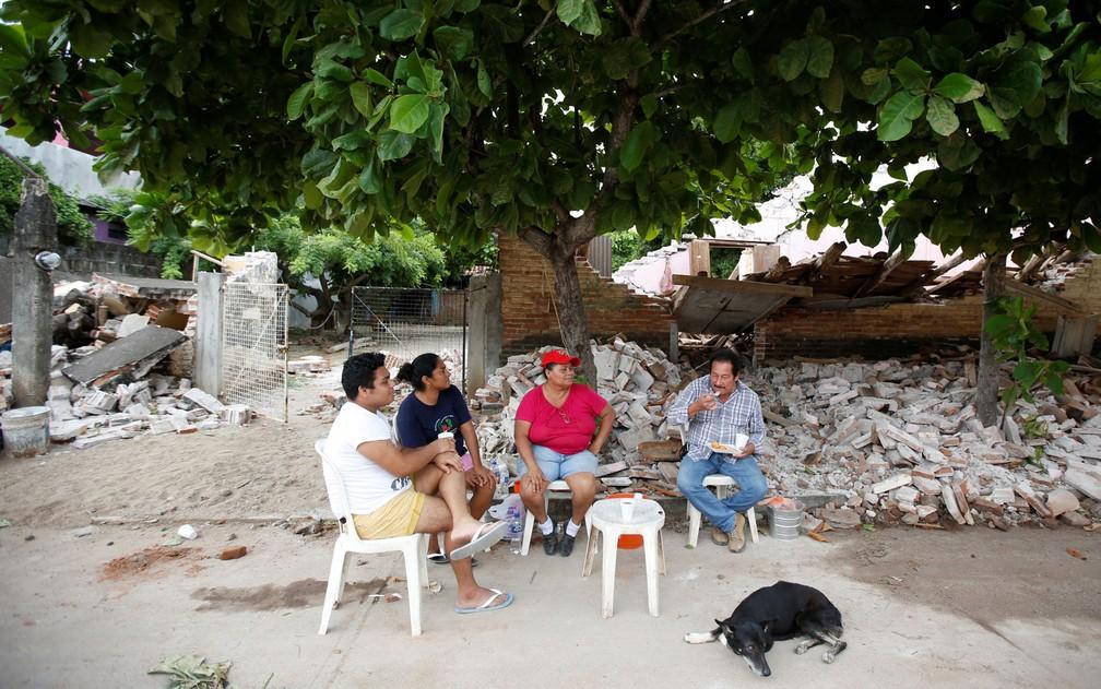 Uma família almoça do lado de for a de sua casa, destruída pelo terremoto de quinta-feira em Ixtaltepec, no México, no domingo (10) (Foto: Reuters/Carlos Jasso)
