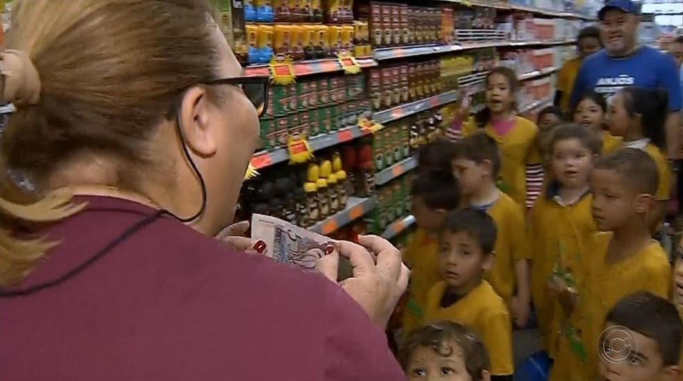 Aparecida Bento de Paula, fundadora do projeto, mostra quanto cada criança tinha para gastar — Foto: TV TEM/Reprodução