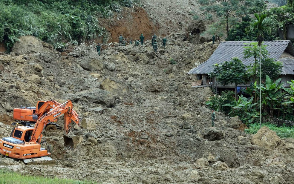 -  Escavadeiras e socorristas procuram por vítimas em área onde houve deslizamento de terra que soterrou quatro famílias em Hoa Binh  Foto: Viet Dung /