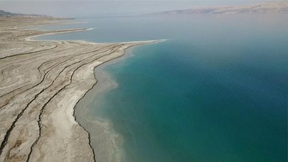 Pesquisador aponta para o potencial turístico dos poços do Mar Morto  (Foto: BBC)