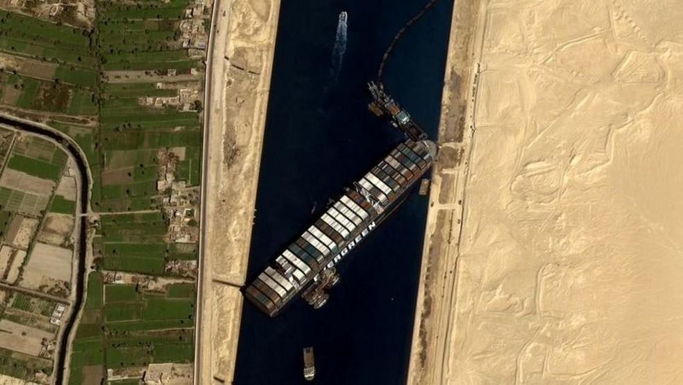Escavadeiras e rebocadores estão sendo usados para desencalhar o navio — Foto: Getty Images via BBC