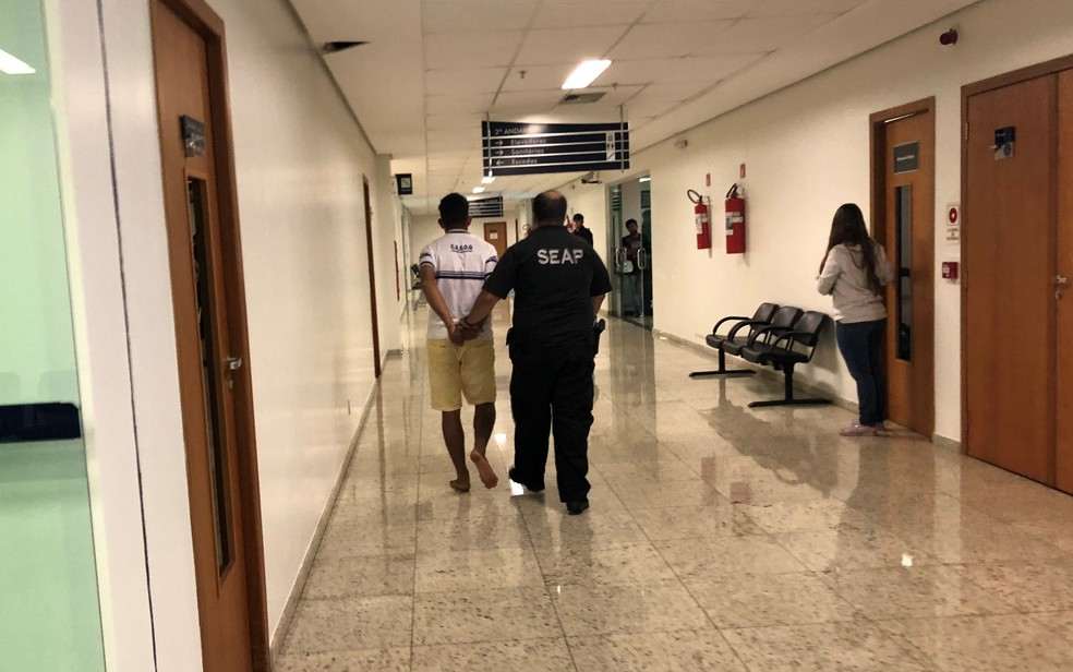 Agente da Superintendência Executiva de Administração Penitenciária de Goiás acompanha estudante de 23 anos após audiência de custódia em Goiânia; juiz decidiu mantê-lo preso por suspeita de estuprar jovem enquanto mantinha mãe dela em cárcere  (Foto: Paula Resende/G1)