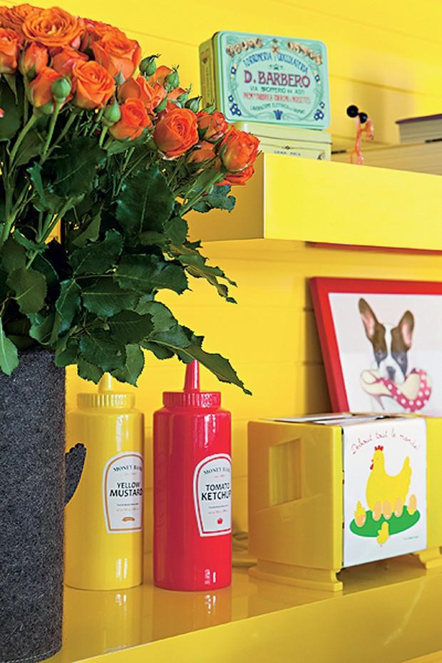 Tubos de ketchup e mostarda e latas antigas viraram objetos de decoração na estante amarela da arquiteta Letícia Arcangeli. O quadro com a imagem de um cachorro comendo sapatos também traz um toque de humor (Foto: Lufe Gomes/Casa e Jardim)