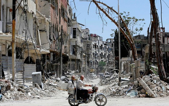 Sírios andam de moto ao longo de uma rua destruída em Douma. Exército sírio declarou que todas as forças antirregime deixaram oleste de Ghouta, após uma ofensiva de dois meses contra os rebeldes (Foto: LOUAI BESHARA/AFP)