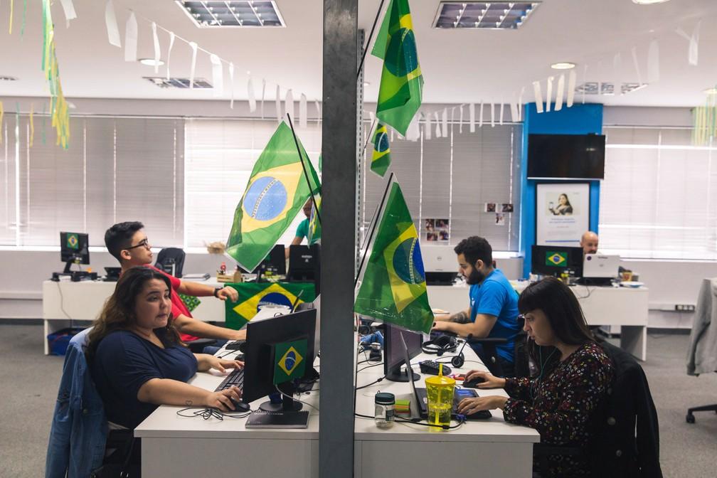 Funcionários trabalham na startup GetNinjas, que enfeitou o ambiente de trabalho para os jogos da Copa do Mundo (Foto: Marcelo Brandt/G1)