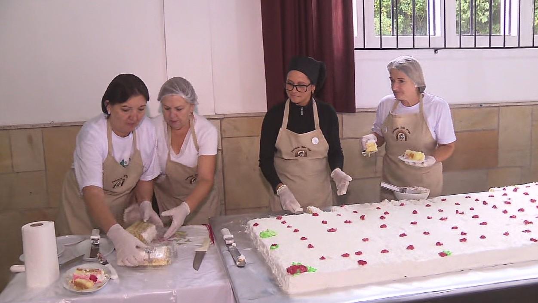 Dia de São Jorge tem bolo de 600 kg com medalhinhas da sorte, em Curitiba