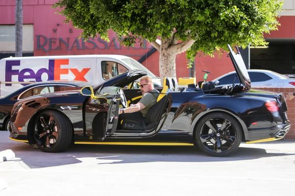 O ator Arnold Schwarzenegger passeando de carro por Los Angeles com um charuto na boca (Foto: Getty Images)
