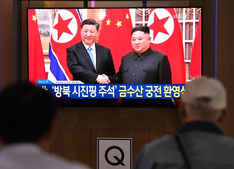 Sul-coreanos assistem pela televisão a imagens do encontro entre o presidente da China, Xi Jinping, e o líder norte-coreano, Kim Jong-un — Foto: Jung Yeon-je/AFP