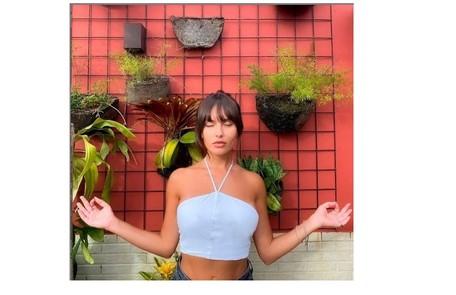 Thaíz Braz posa em cantinho com plantas. Recentemente, a imagem foi usada para brincar com a fase 'namastreta' da confinada do 'BBB' Reprodução