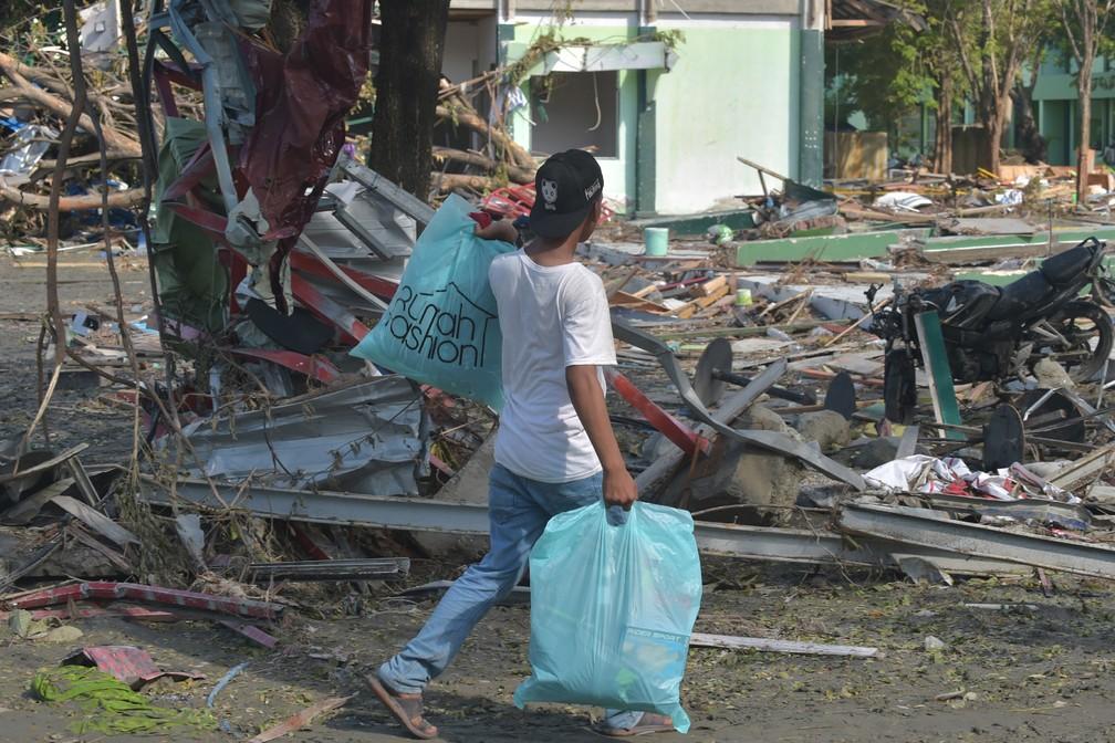 Um homem carrega sacos com itens de uma loja em Palu, na Indonésia, após o terremoto e tsunami neste sábado (30) — Foto: Adek Berry/AFP