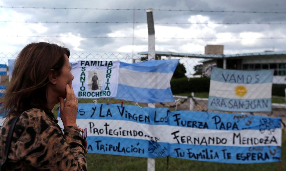 Mulher observa faixas de apoio aos tripulantes do submarino ARA San Juan (Foto: Marcos Brindicci/Reuters)
