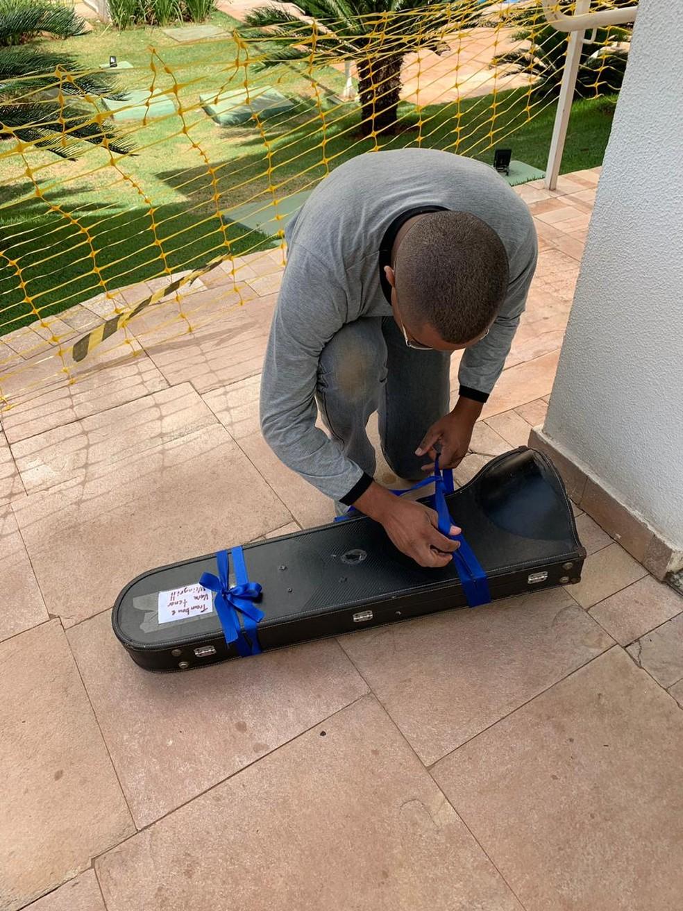 Momento em que Raphael recebe trombone de moradores de condomínio, em Campo Grande. — Foto: Elizangela Roberto