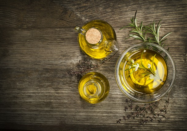 Olive oil with fresh herbs on wooden background. (Foto: Getty Images/iStockphoto)