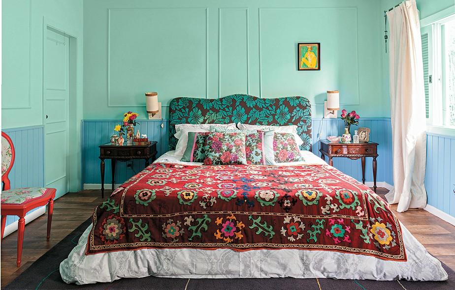 A base mais calma, com verde e azul lavados, permitiu a designer de interiores Neza Cesar ousar nas estampas da cama. A cabeceira de veludo faz contraste com as almofadas e a manta. Repare que todos os desenhos, apesar de diferentes, são florais