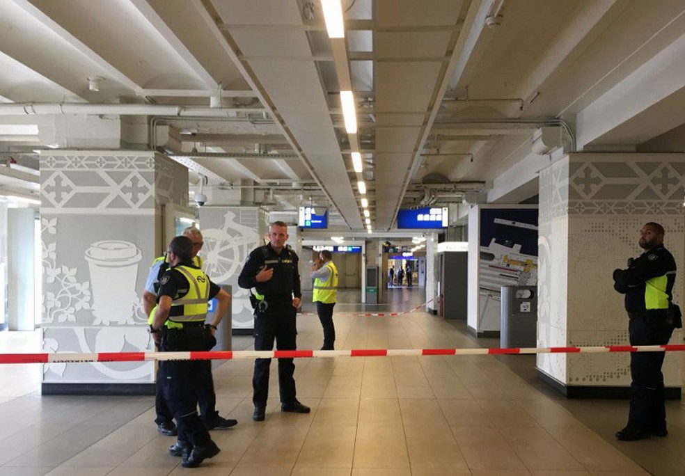 Policiais fazem patrulha na Estação Ferroviária Central de Amsterdã, na Holanda, depois que duas pessoas ficaram feridas com faca, nesta sexta (31). Suspeito foi baleado pela polícia  (Foto: Germain Moyon / AFP)