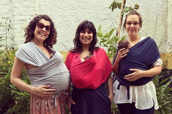 Julia ao centro com a irmã Flor à esquerda e a amiga Joana, todas passeando com os bebês no sling (Foto: Acervo pessoal)