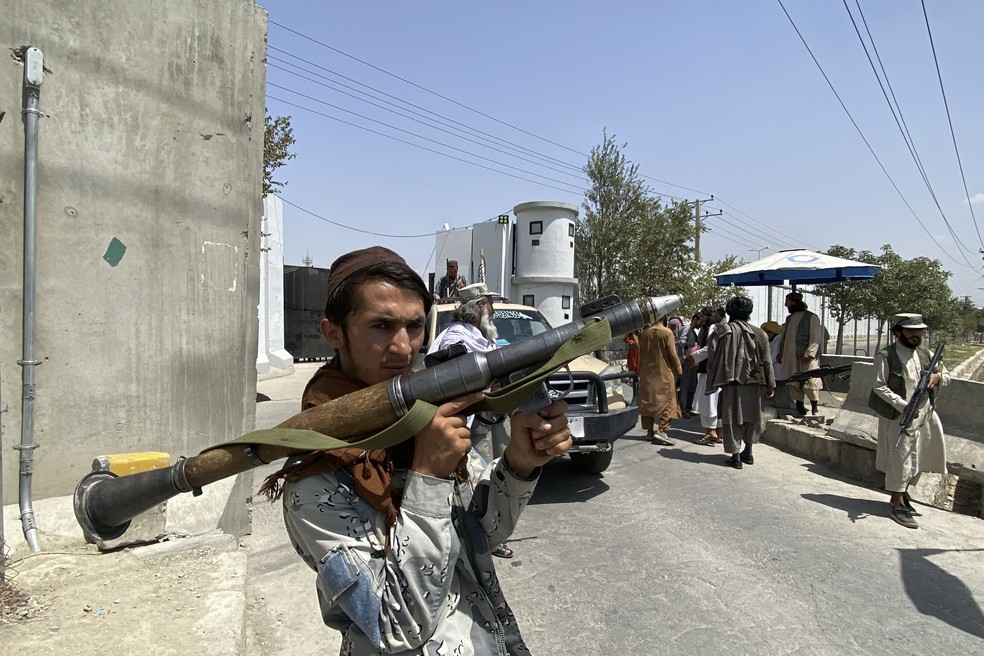 Talibã segura armamento na entrada do Ministério do Interior em Cabul, no Afeganistão — Foto: Javed Tanveer / AFP