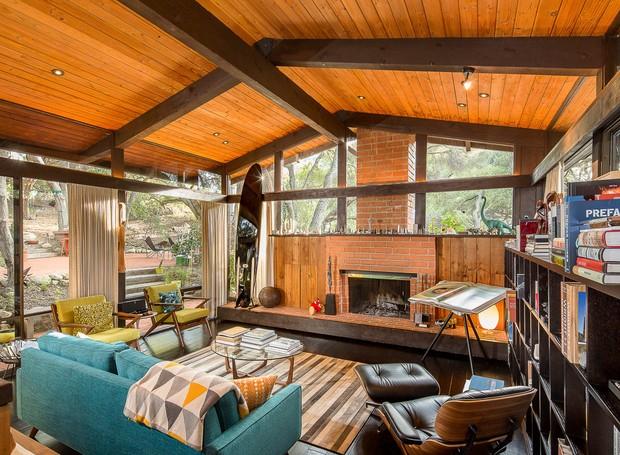 As janelas trazem a iluminação natural, enquanto a madeira, a lareira e o sofá deixam o ambiente mais aconchegante (Foto: Shawn Bishop Photography/ Reprodução)