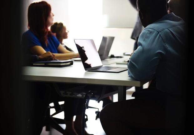 Jovens usando notebooks em uma mesa (Foto: Pexels)