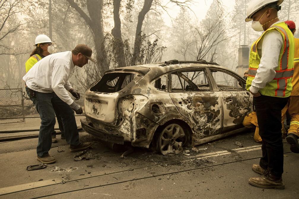 Homem vasculha, com bombeiros, carro de amigo consumido pelo fogo no norte da Califórnia — Foto: Noah Berger/AP Photo