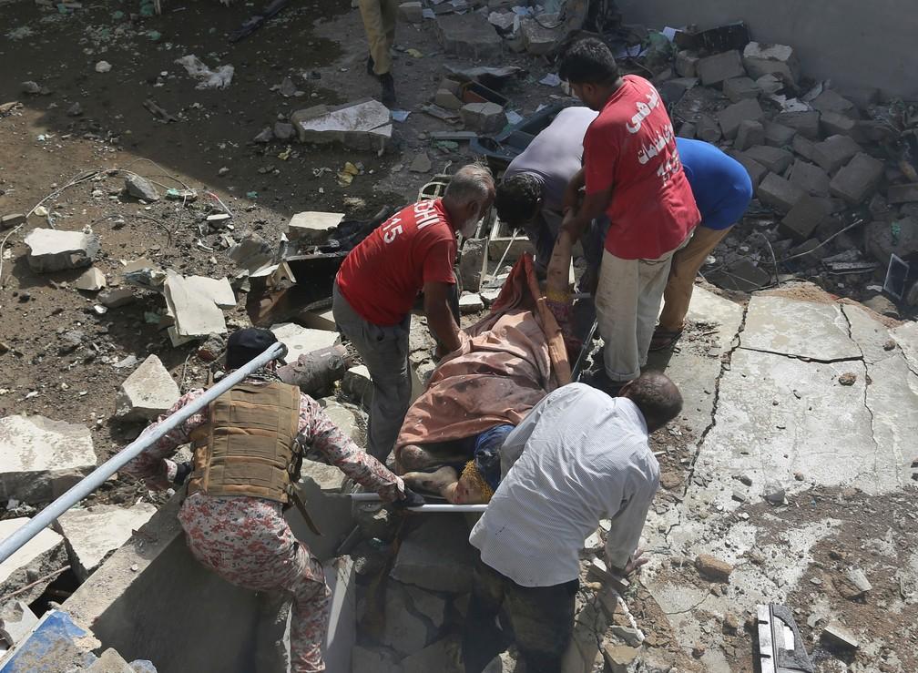 Voluntários carregam corpo de vítima de queda de avião em Karachi, no Paquistão, nesta sexta-feira (22)  — Foto: Khan Fareed/AP