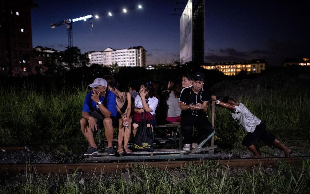 Foto de 19 de outubro mostra pessoas sendo transportadas em carrinho de passageiros em linha de trem de Manila — Foto: Noel Celis/AFP