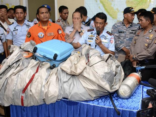 30/12 - Comandante indonésio apresenta objetos retirados do mar que pertenciam ao voo 8501 da AirAsia, como uma mala azul e o que parece ser um tanque de oxigênio, na base aérea de Pangkalan Bun (Foto: Dewi Nurcahyani/AP)