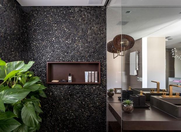 Banheiro da suíte principal tem box revestido em pedra escura e plantas (Foto: Fran Parente/Divulgação)