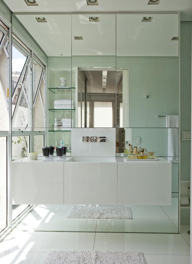 No projeto de Simone Mantovani, o banheiro de tons claros e com parede de espelhos dá a sensação de amplitude. Repare que a bancada suspensa com gavetões otimiza o espaço. (Foto: Edu Castello / Casa e Jardim)