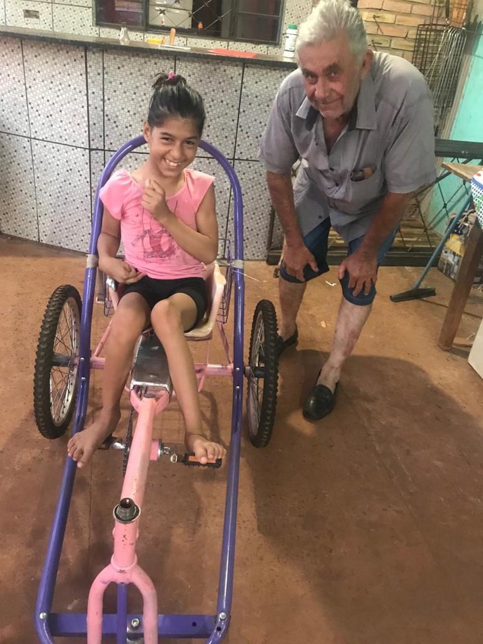 Clóvis e a neta com a bicicleta e adpatada, em Sidrolândia (MS). — Foto: Roseli Bonfim Acunha/Arquivo pessoal