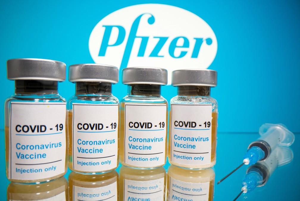 Foto ilustrativa com frascos e seringa na frente de logotipo da farmacêutica Pfizer — Foto: Dado Ruvic/Reuters