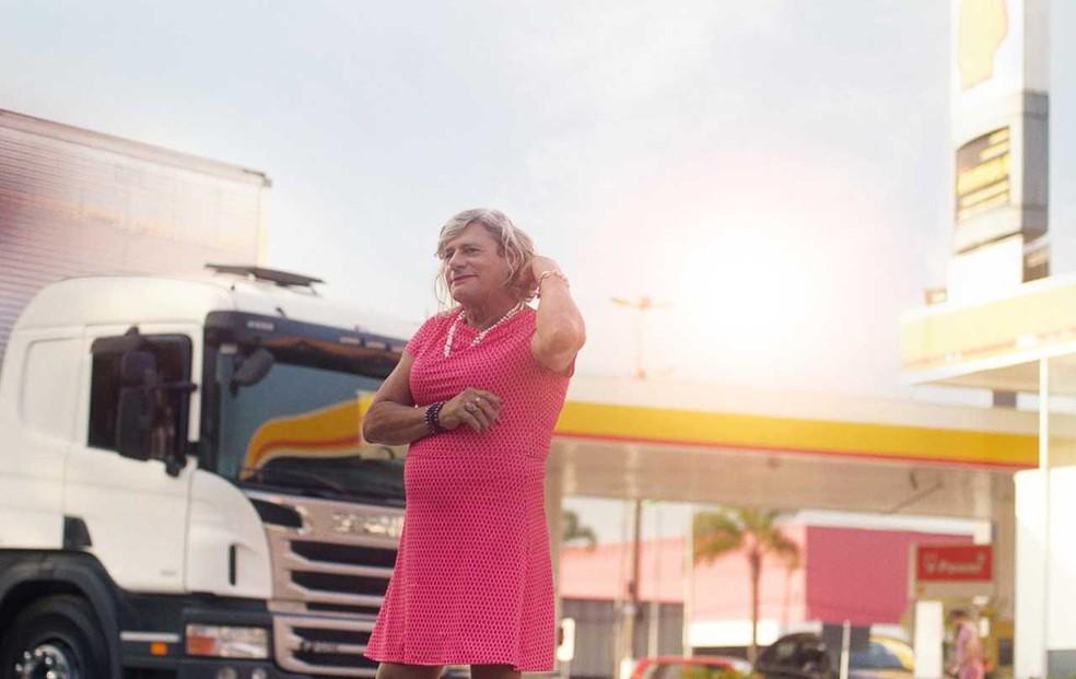 Afrodite viaja em um caminhão de vestido, de salto alto e maquiada — Foto: Shell/Divulgação