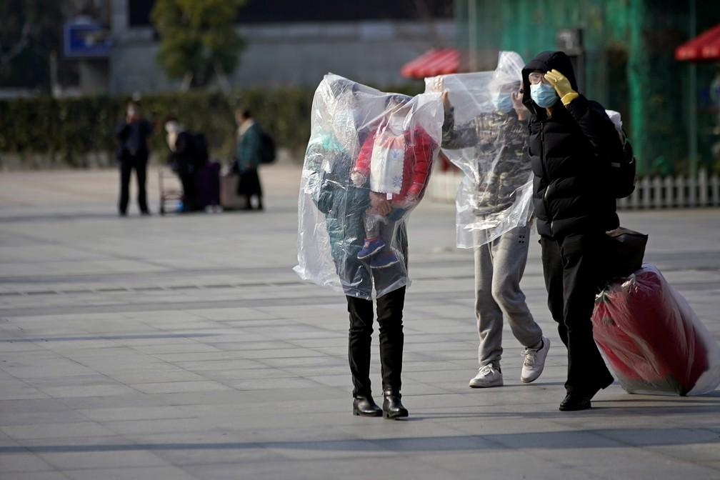 Família se envolve em sacolas plásticas para tentar se proteger de epidemia de coronavírus em Xangai, China — Foto: Aly Song/Reuters