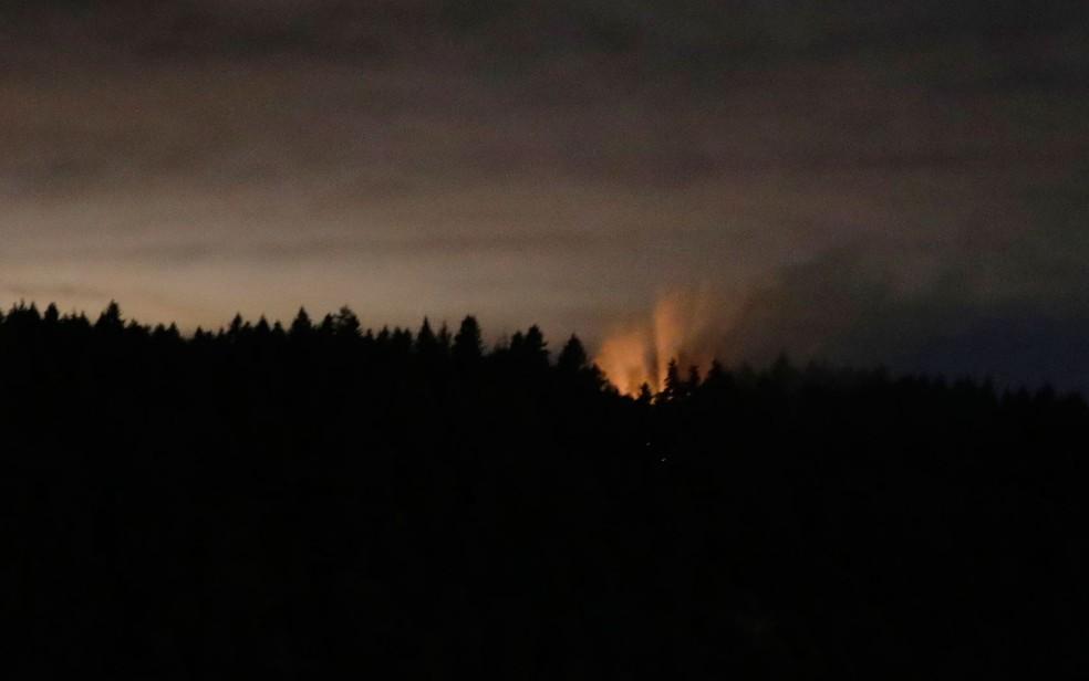 Clarão e fumaça são vistos em local onde caiu avião roubado por funcionário da Horizon Air, perto de Washington, na madrugada de sábado (11)  (Foto: AP Photo/Ted S. Warren)