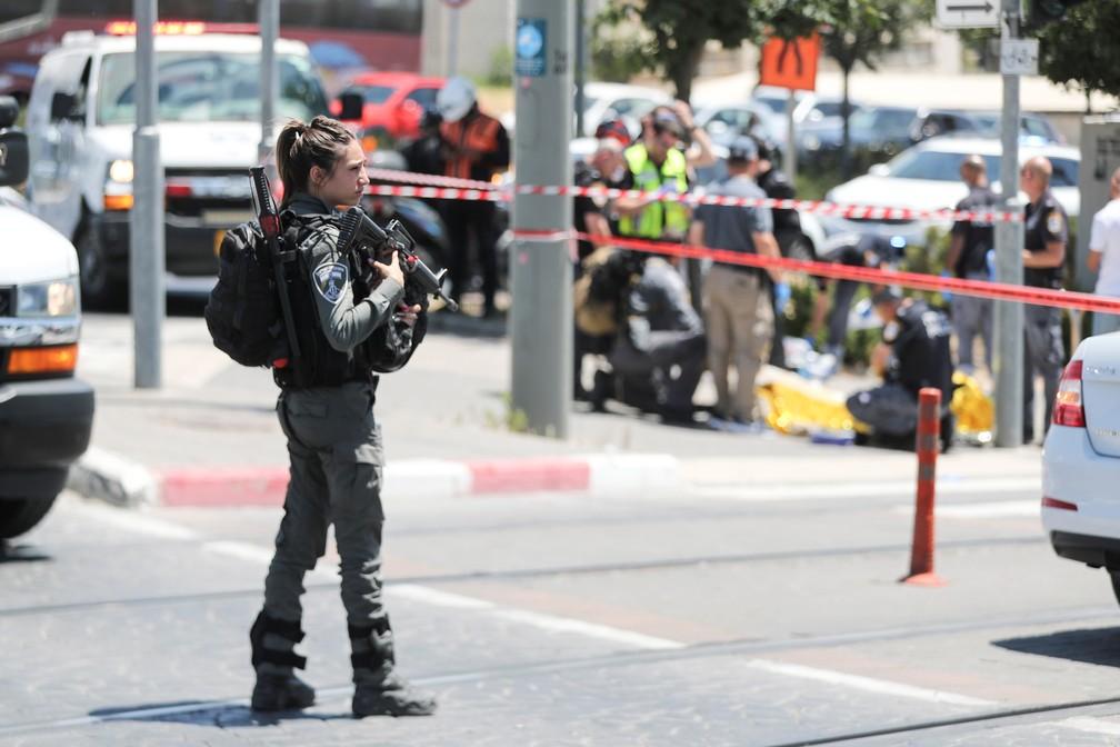 Agente das forças de segurança israelense guarda local de ataque a facas em Jerusalém enquanto equipe trabalha na cena do crime (ao fundo) nesta segunda (24) — Foto: Ammar Awad/Reuters