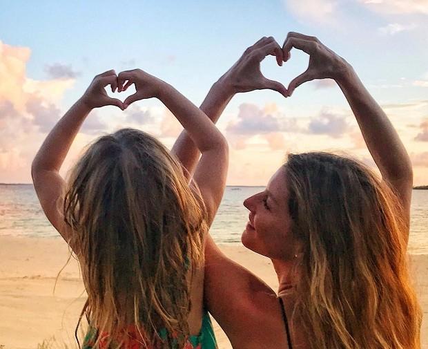Gisele e Vivian fazem corações com as mãos em praia (Foto: Reprodução/Instagram)