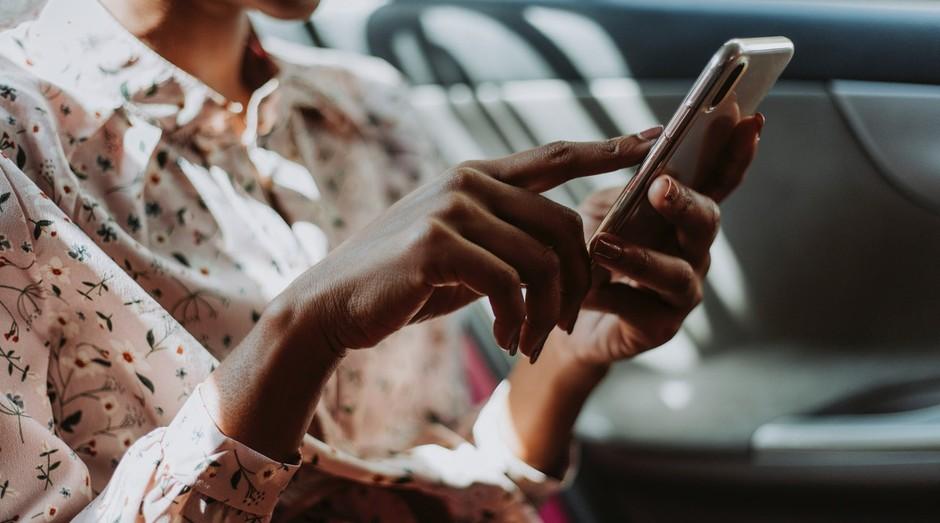 Mulher usa celular dentro de carro; transporte; uber (Foto: Pexels)