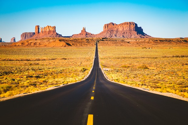 Classic panorama view of historic U.S. Route 163 running through famous Monument Valley in beautiful golden evening light at sunset in summer, Utah, USA (Foto: Getty Images/iStockphoto)
