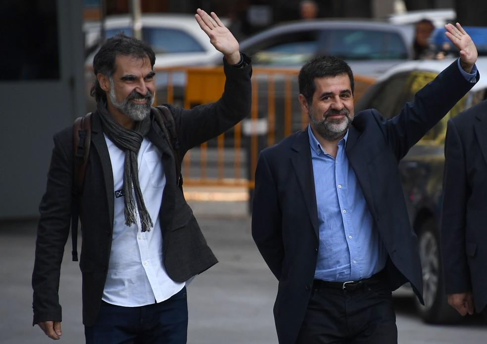 Líderes separatistas catalães Jordi Sánchez e Jordi Cuixart acenam ao chegar na Suprema Corte em Madri nesta segunda-feira (16) (Foto: GABRIEL BOUYS / AFP)