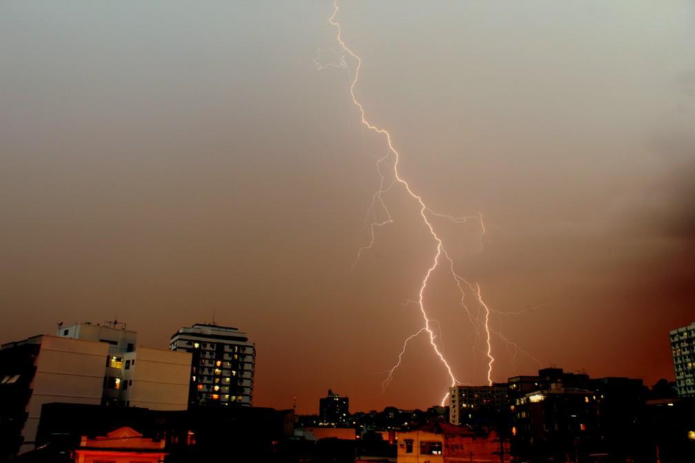 Renata Ferreira Tavares mostra a queda de um raio no céu alaranjado do Rio de Janeiro — Foto: Renata Ferreira Tavares/Inpe