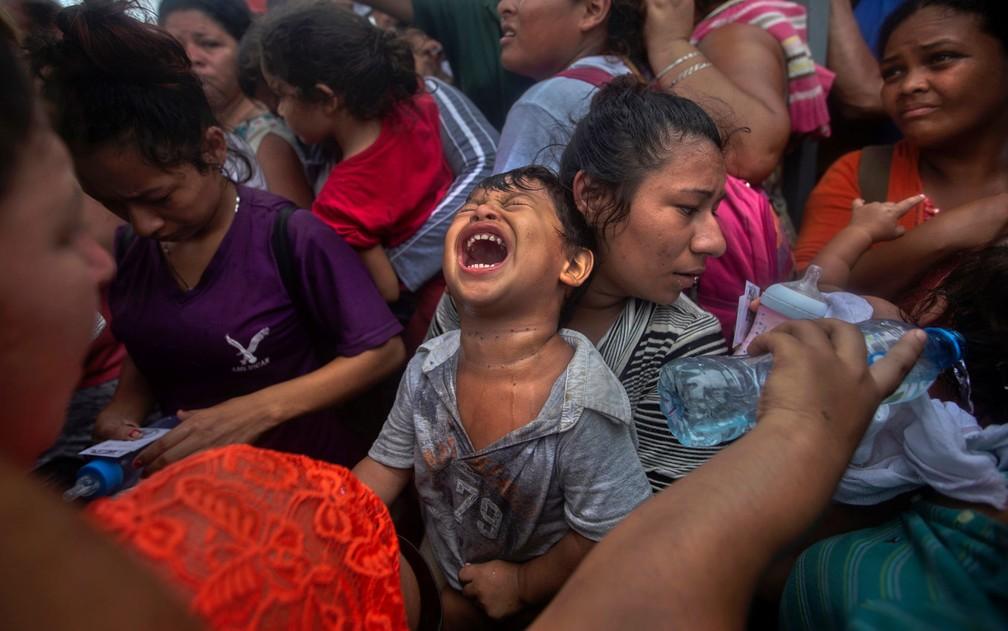Um menino migrante, parte de caravana da América Central que tentava chegar aos EUA, chora pelo excesso de calor e umidade em ponto de checagem na fronteira entre Guatemala e México, em Ciudad Hidalgo, em 20 de outubro de 2018 — Foto: Reuters/Edgard Garrido/File Photo